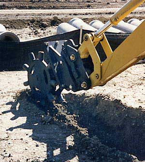 Compaction wheel compacting soil in trench after excavation. Five year guarantee on compaction wheels for skid steers, excavators, and backhoes.